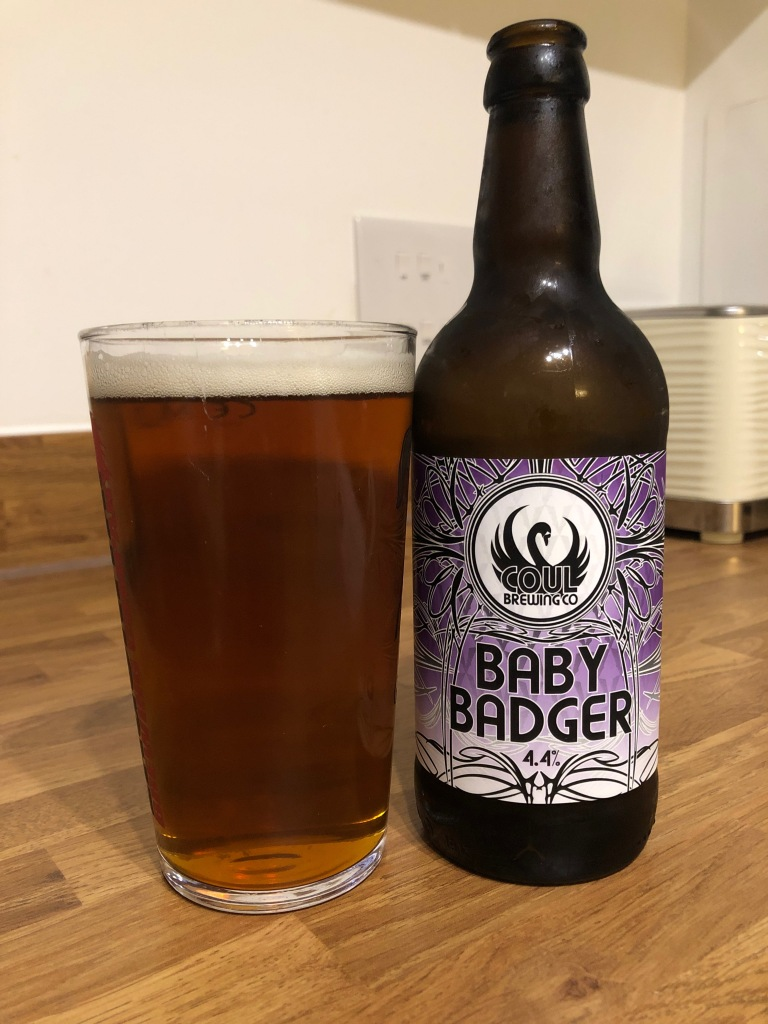 """A pint of beer and a bottle with text saying """"Coul Brewing Co BABY BADGER 4.4%"""""""